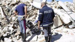 Tre poliziotti cercano oggetti tra le rovine della casa dove, a causa del terremoto, ha trovato la morte un loro collega,  Amatrice, 25 agosto 2016.  ANSA/FLAVIO LO SCALZO