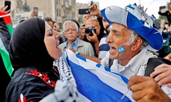 Un uomo israeliano discute animatamente con una donna palestinese