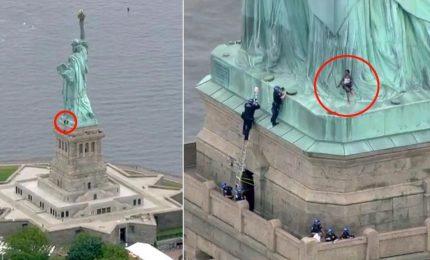 Una donna scala la Statua della Libertà contro Trump